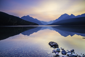 Bowman Lake, Sunrise, layered mountains, clear water, reflection, rocks, pink sky, Glacer national Park, montana