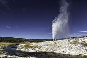 Beehive Geyser erupting as the Firehole River winds around it